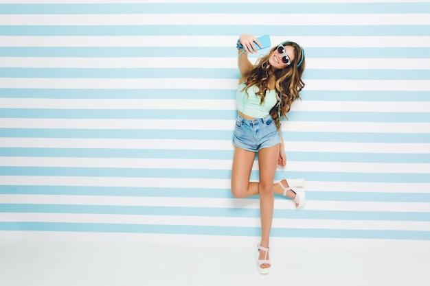 Langhaariges gebräuntes mädchen, das jeansshorts und sandaletten trägt, die auf einem bein stehen und selfie mit einem lächeln machen. porträt der jungen frau in voller länge in der sonnenbrille, die auf gestreifter wand aufwirft.