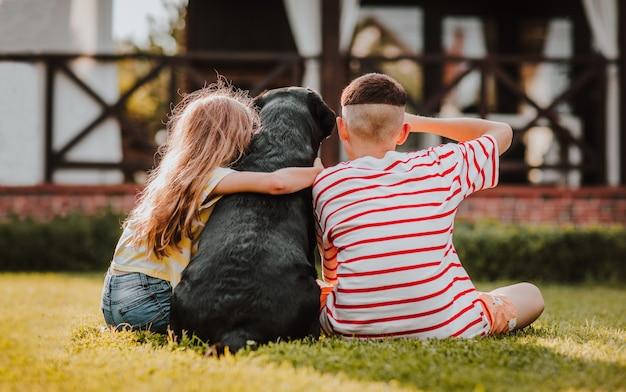 Langhaariges junges mädchen und hipster-teen-junge in abgestreiften sommerhemden, die mit dem rücken auf grünem gras mit schwarzem labrador-retriever sitzen. ansicht von hinten.