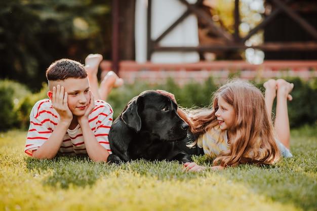 Langhaariges junges mädchen und hipster-teen-junge in abgestreiften sommerhemden, die mit schwarzem labrador retriever auf grünem gras liegen.