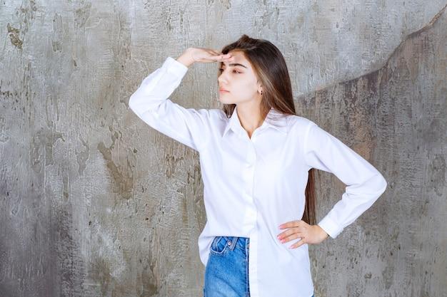 Langhaariges schönes mädchen in weißer bluse, das irgendwo hinschaut