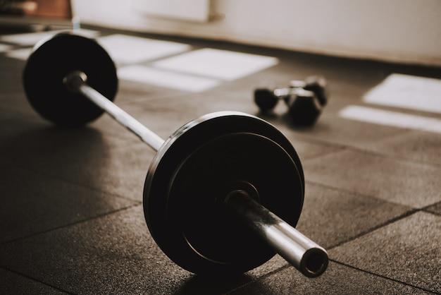 Langhantel und hanteln liegt auf dem boden im fitnessstudio