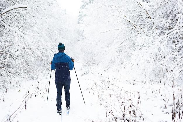 Langlauf im winterwald, skifahrer in hut mit pompon mit skistöcken
