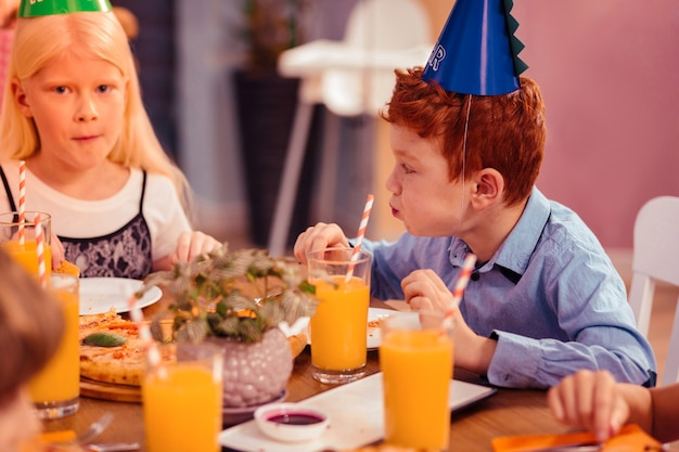 Langsam essen. aufmerksames blondes mädchen, das am tisch sitzt