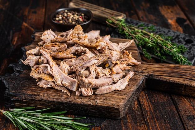 Langsam gekochtes schweinefleisch auf einem holzbrett mit metzgerbeil. dunkles holz