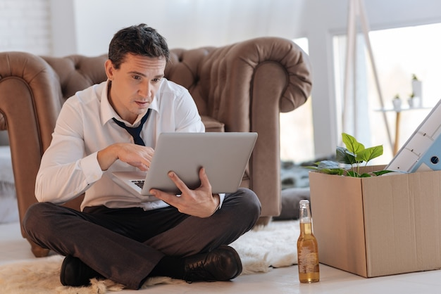Langweilige arbeit. müder gelangweilter junger mann, der mit gekreuzten beinen auf dem boden sitzt und auf den bildschirm seines laptops schaut, während eine flasche bier und eine schachtel mit verschiedenen gegenständen an seiner seite stehen