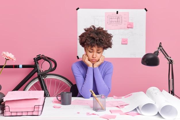 Langweilige hausaufgaben. traurige unzufriedene junge beschäftigte afroamerikanerin fühlt sich müde von routinearbeitsposen auf dem desktop, umgeben von blaupausen, skizziert eine tasse kaffee