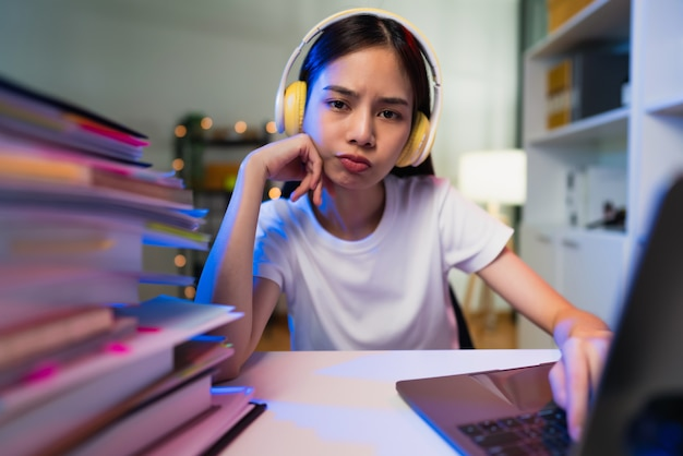 Langweilige junge frau mit headset und handeingabe auf der tastatur mit dokumentdatei auf dem tisch, die am computer arbeitet, macht jeden tag die gleiche arbeit.