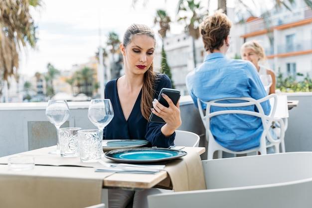 Langweiliges junges mädchen, das auf ihr date wartet, das an einem tisch in einem restaurant im freien sitzt