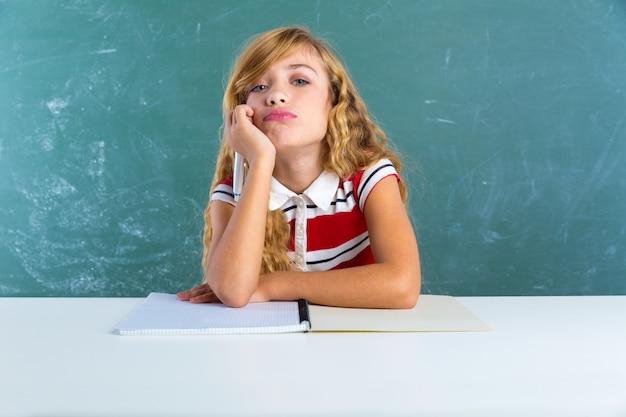Langweiliges trauriges ausdruckstudentenschulmädchen auf schreibtisch