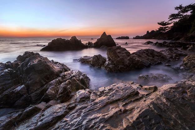 Langzeitbelichtung sonnenaufgang seelandschaft mit erstaunlichen rock textur.