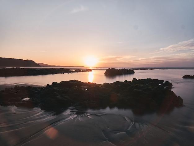 Langzeitbelichtung sonnenuntergang mit felsen im vordergrund von seidigem wasser und die reflexion der sonne gebadet.