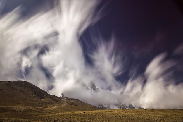 Langzeitbelichtung von sich schnell bewegenden wolken und blauem himmel über himalaya-bergen