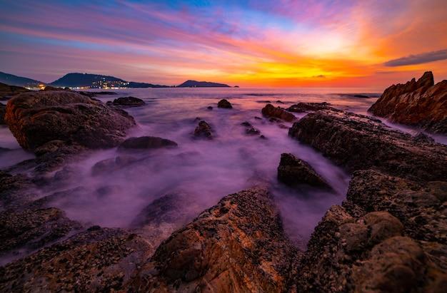 Langzeitbelichtungsbild der dramatischen himmelsseelandschaft mit felsen im vordergrundsonnenuntergang oder im sonnenaufgang über dem hintergrund der seelandschaft.