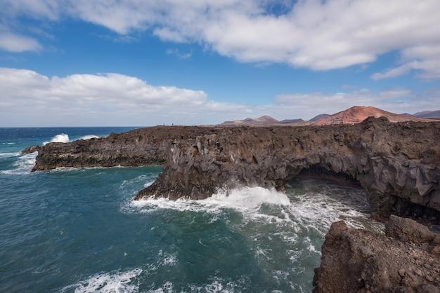 Lanzarote landschaft. los hervideros küste, lavahöhlen, klippen und wellenförmigen ozean.