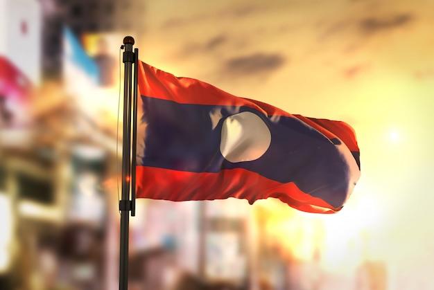 Laos-flagge gegen stadt verschwommen hintergrund bei sonnenaufgang hintergrundbeleuchtung