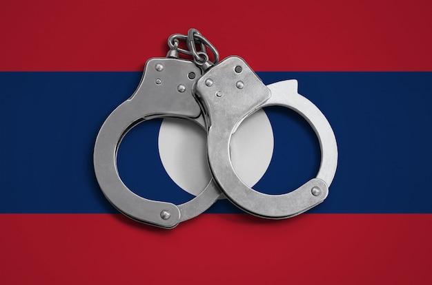Laos flagge und polizei handschellen. das konzept der einhaltung des gesetzes im land und des verbrechensschutzes