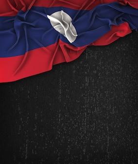 Laos-flagge vintage auf einem grunge-schwarz-tafel mit platz für text