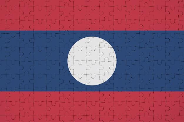 Laos-flagge wird auf einem gefalteten puzzlespiel dargestellt