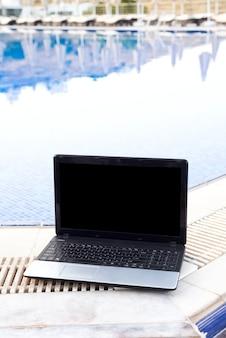 Laptop am pool, der das sunbed übersieht, arbeiten am feiertagssommerkonzept