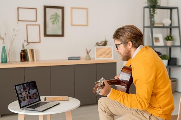 Laptop-anzeige mit fleißigem teenager-mädchen, das gitarre spielt, während auf couch in der häuslichen umgebung während der online-lektion mit lehrer sitzt