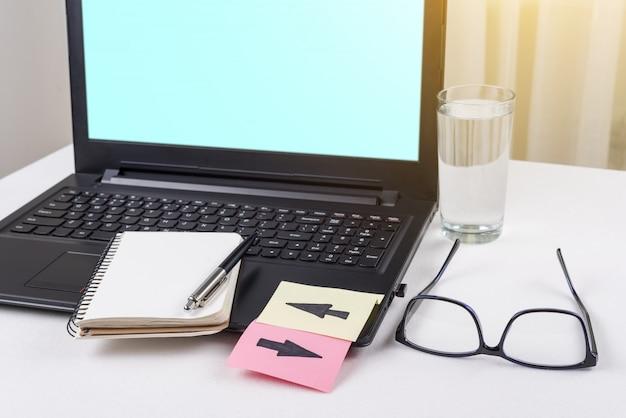 Laptop auf dem schreibtisch, auf der tastatur sind aufkleber mit pfeilen aufgeklebt.