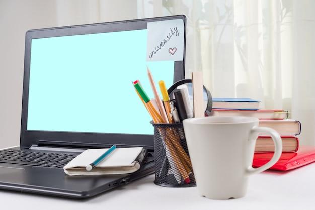 Laptop auf dem schreibtisch des studenten, auf der monitoraufkleberuniversität.