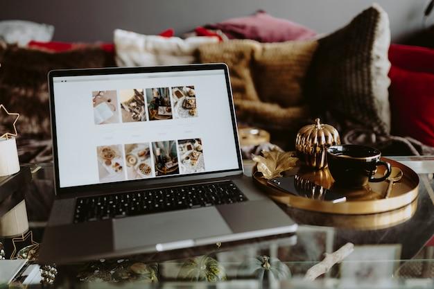Laptop auf einem glastisch, der eine fotozufuhr zeigt