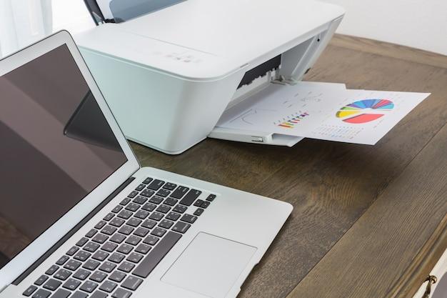 Laptop auf einem holztisch mit einem drucker