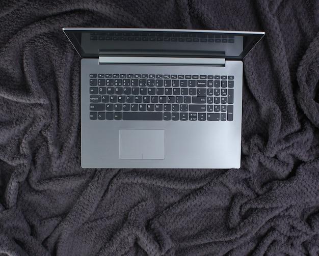 Laptop auf einer warmen decke. draufsicht.