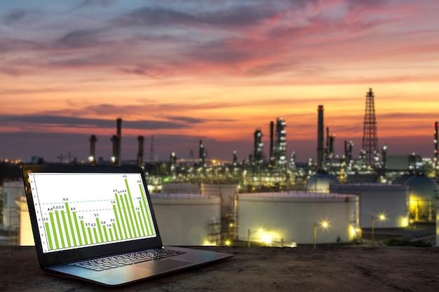 Laptop auf holztisch mit ölraffineriehintergrund