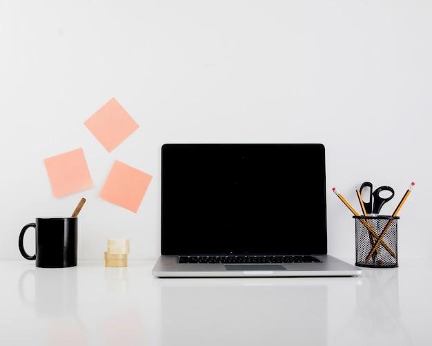 Laptop auf reflektierendem schreibtisch im büro