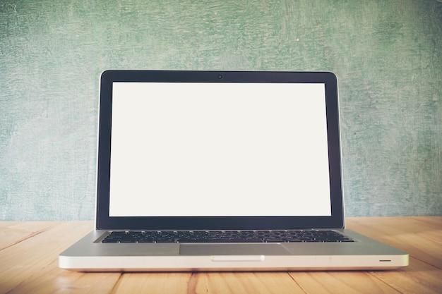 Laptop auf tabelle, auf tafelhintergrund, leerer bildschirm