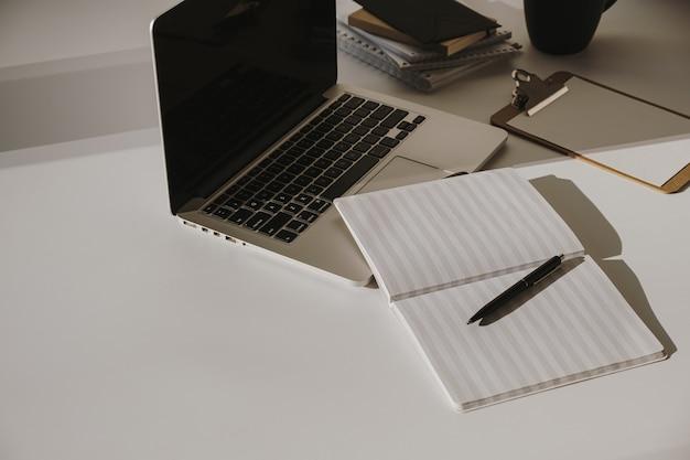 Laptop auf tisch mit kaffeetasse, papierblatt gegen weiße wand