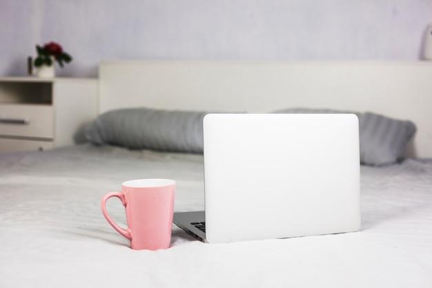 Laptop auf weißem bett mit kaffeetasse