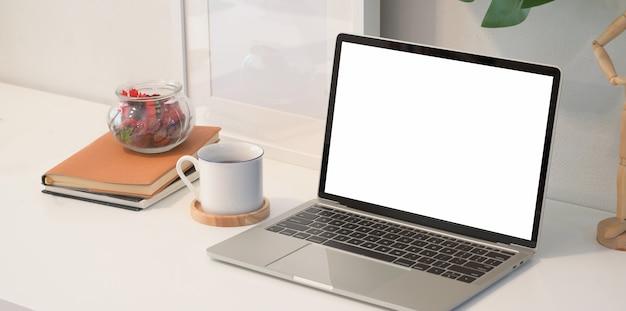 Laptop auf weißem hölzernem schreibtisch im kreativen studio