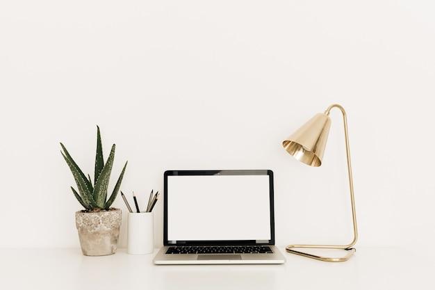 Laptop auf weißem tisch mit goldener lampe und aloe-pflanze.