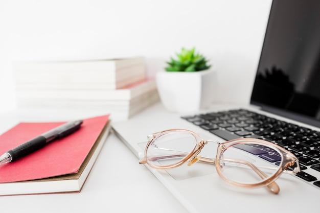 Laptop; brille; stift und tagebuch auf schreibtisch