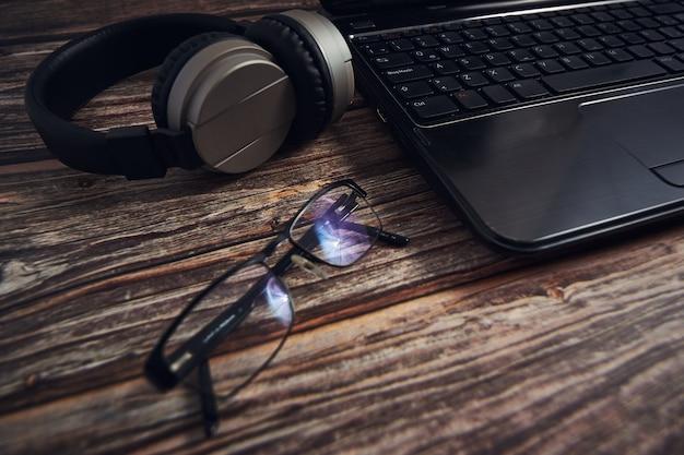Laptop-brille und kopfhörer auf einem holzschreibtisch