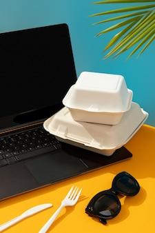 Laptop, brotdose und besteck auf orange tisch. online-konzept für die lieferung von lebensmitteln