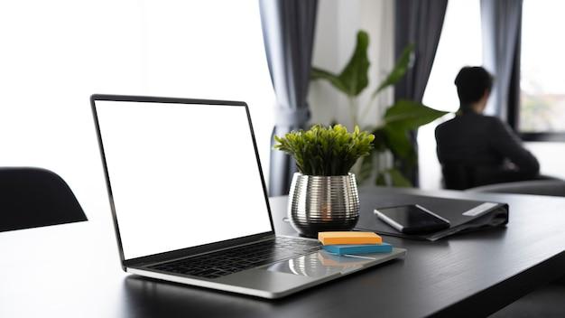 Laptop-computer auf schreibtisch und geschäftsmann, die im hintergrund sitzen.