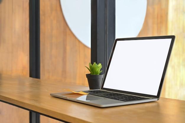 Laptop-computer lokalisierter weißer schirm auf hölzernem regal.