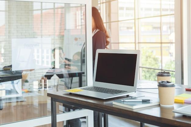 Laptop-computer mit geöffnetem deckel auf tisch im besprechungsraum des büroarbeitsbereichs.