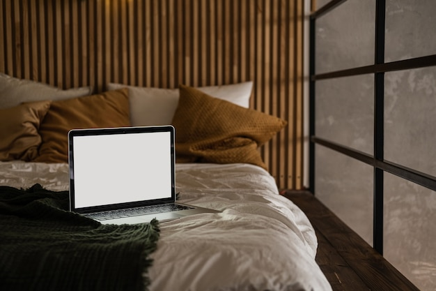 Laptop-computer mit leerem bildschirm im bett mit kissen und bettwäsche.