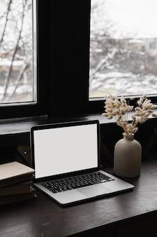 Laptop-computer mit leerer kopienraum-bildschirmanzeige auf tablette mit hasenschwanzgrasblumenstrauß gegen fenster spott oben.