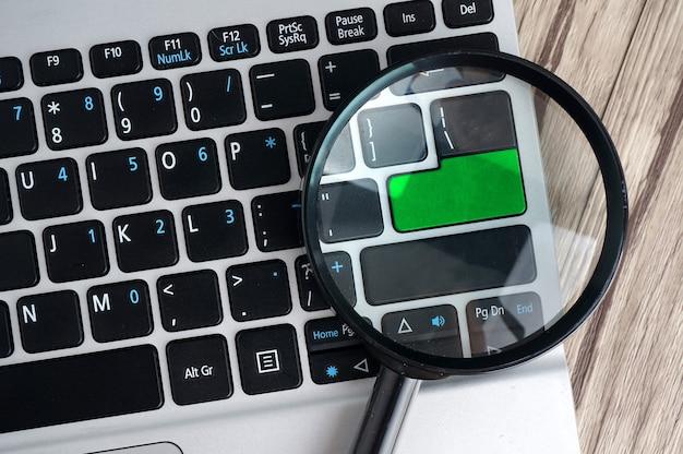 Laptop-computer mit lupe, suchkonzept