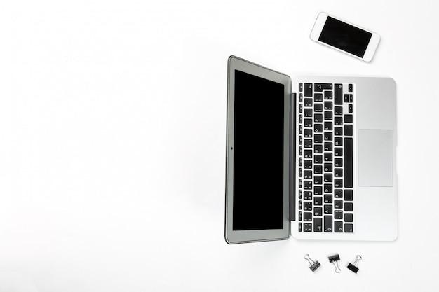 Laptop-computer mit mobiltelefon und schwarzen büroklammern auf weißer oberfläche.