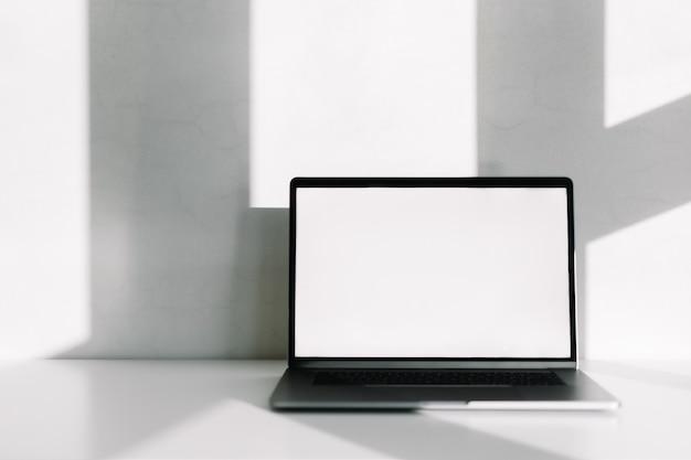 Laptop-computer mit weißem leerem bildschirm auf dem weißen tisch mit schatten vom fenster.