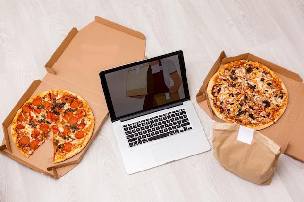 Laptop-computer-nahaufnahme mit einer appetitlichen pizza