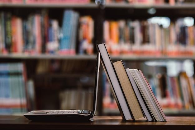 Laptop-computer und buch am arbeitsplatz im bibliotheksraum