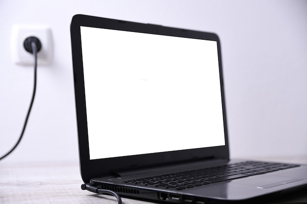 Laptop, computer wird über eine 220-volt-steckdose auf einem schreibtisch in der nähe der wand aufgeladen. energie, akkumulation. attrappe, lehrmodell, simulation
